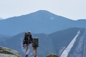 Two hikers walking toward a mountain