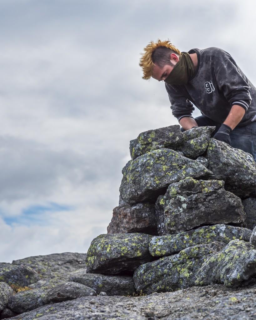 A man building a rock cairn