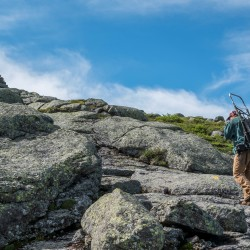 A woman climbs a rocky mountain with a pack