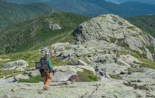 A woman walking down a mountainside