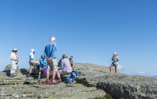 A woman talks to a group of hikers
