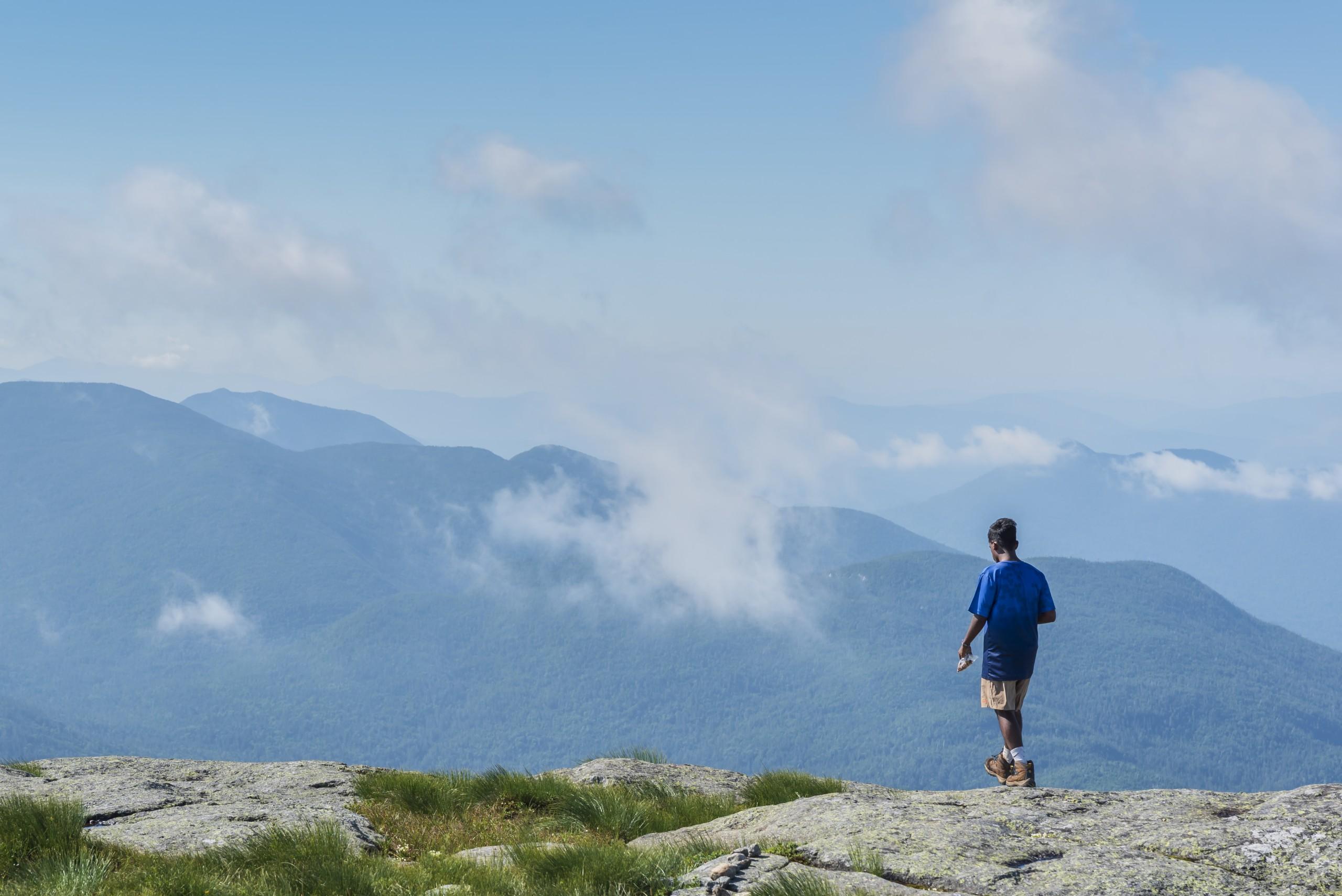 A boy walking on a mountain summit
