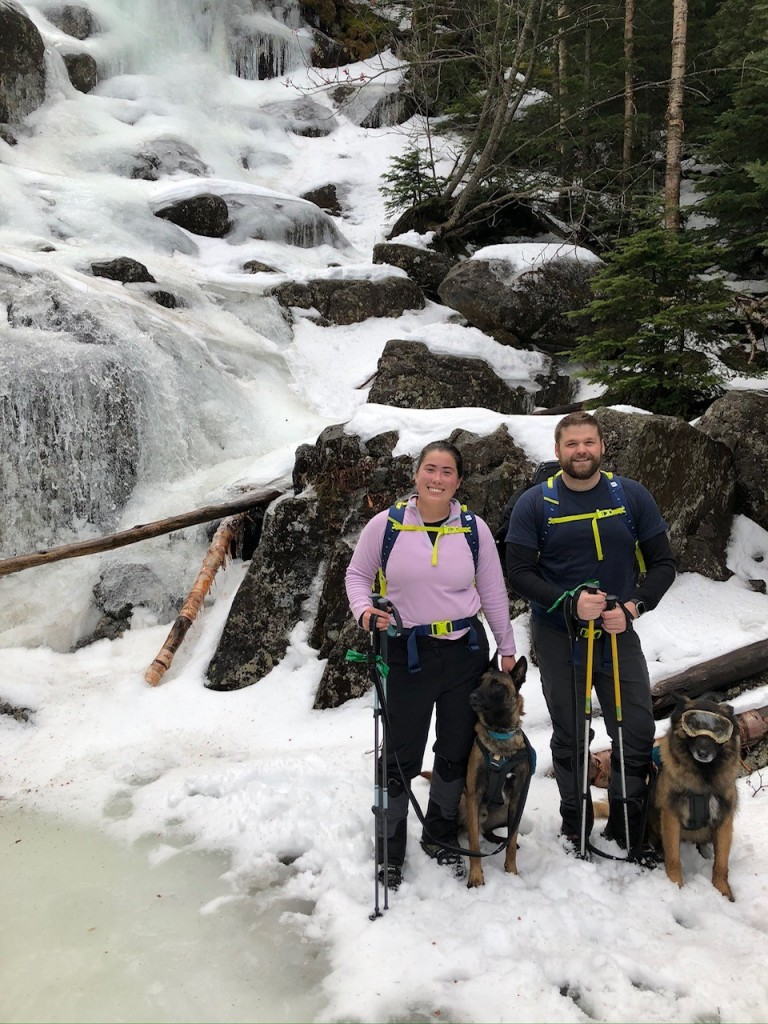 Two hikers and a dog stand on ice