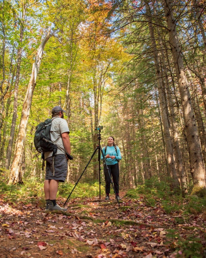 Two people standing in the woods with a tripod