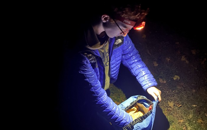 A boy using a headlamp to look through his backpack
