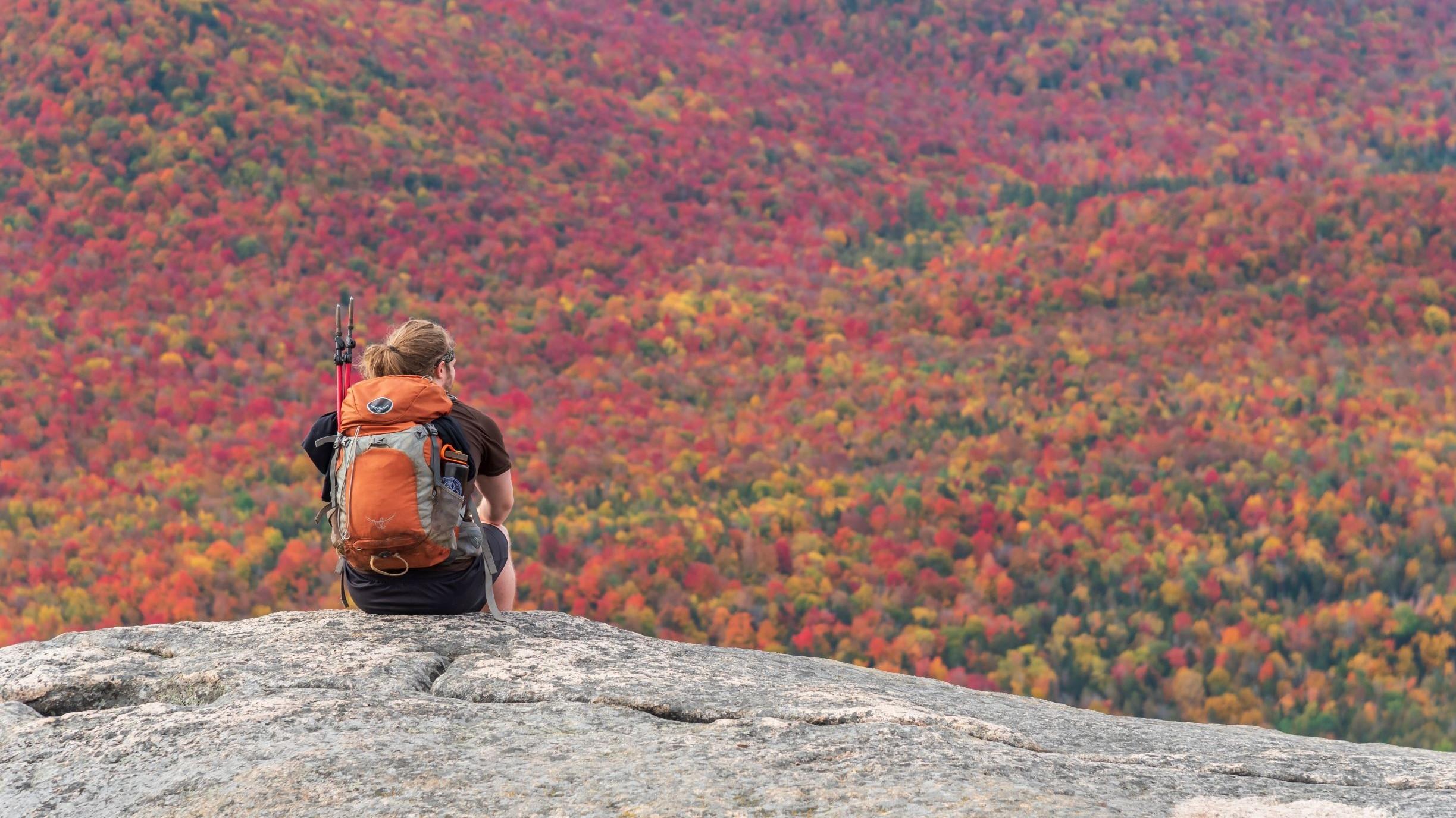 A man sits on a summit