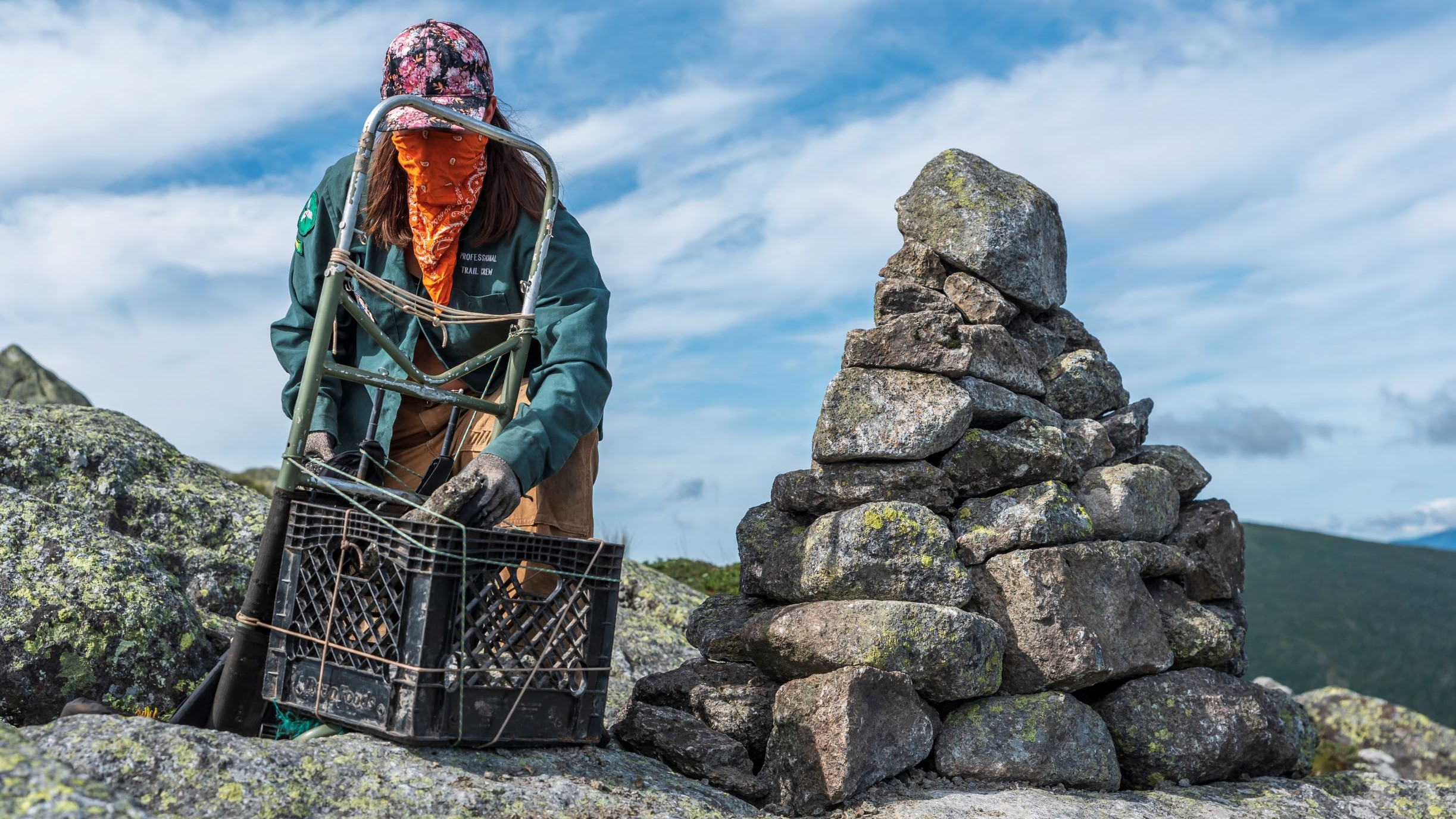 A person stacking rocks in a pack frame next to a cairn