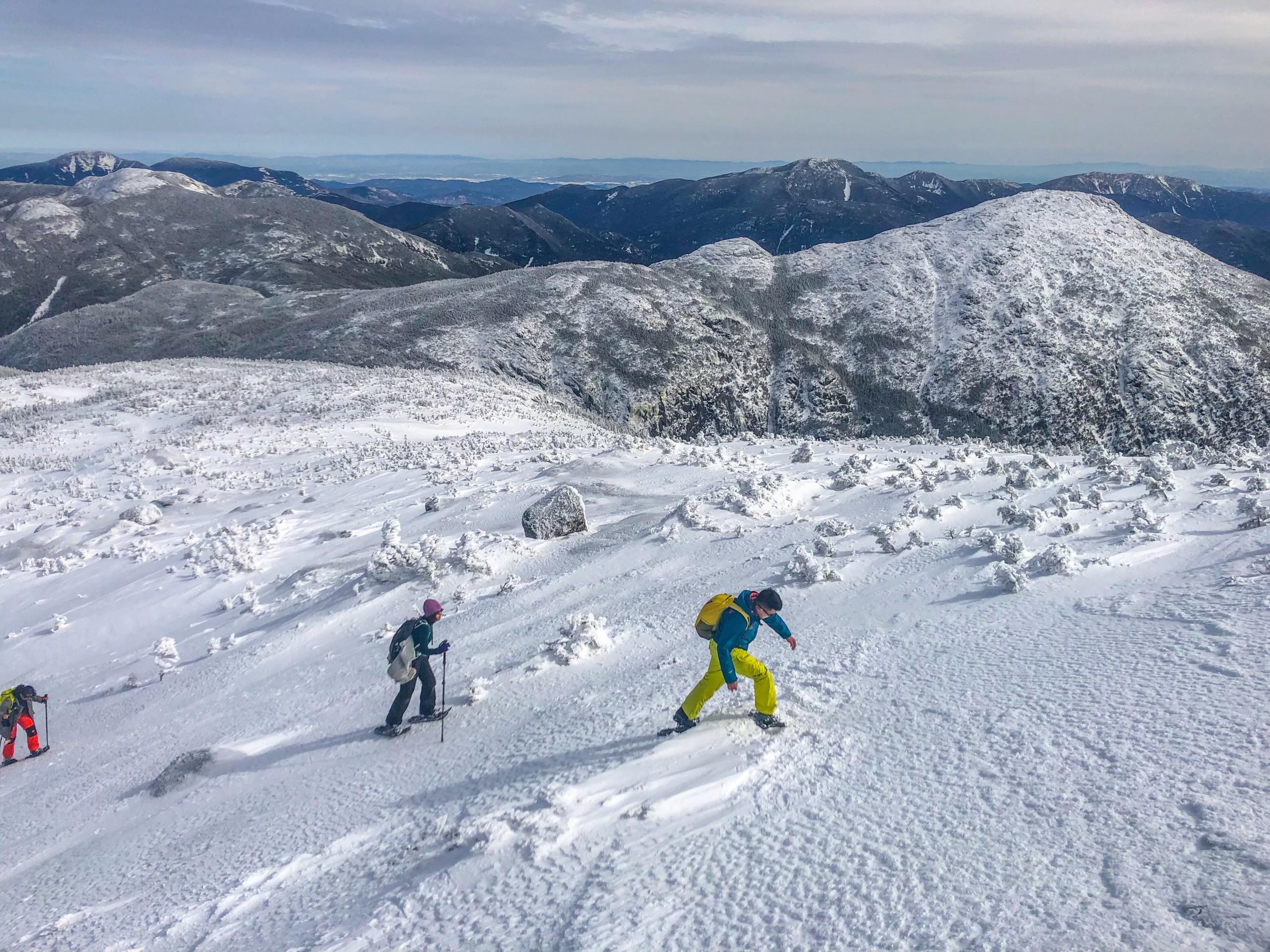 Three people walking on a snowy mountain ridgeline