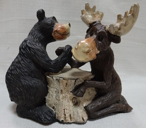 Moose and bear arm wrestling on a tree stump