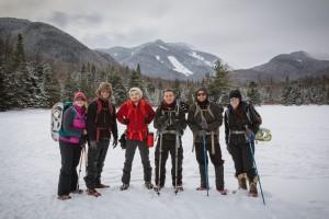Six people standing in a snowy field