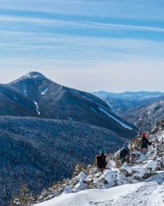 Three hikers walk in a snowy landscape