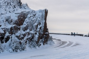 A bend in a snowy road with two skiers