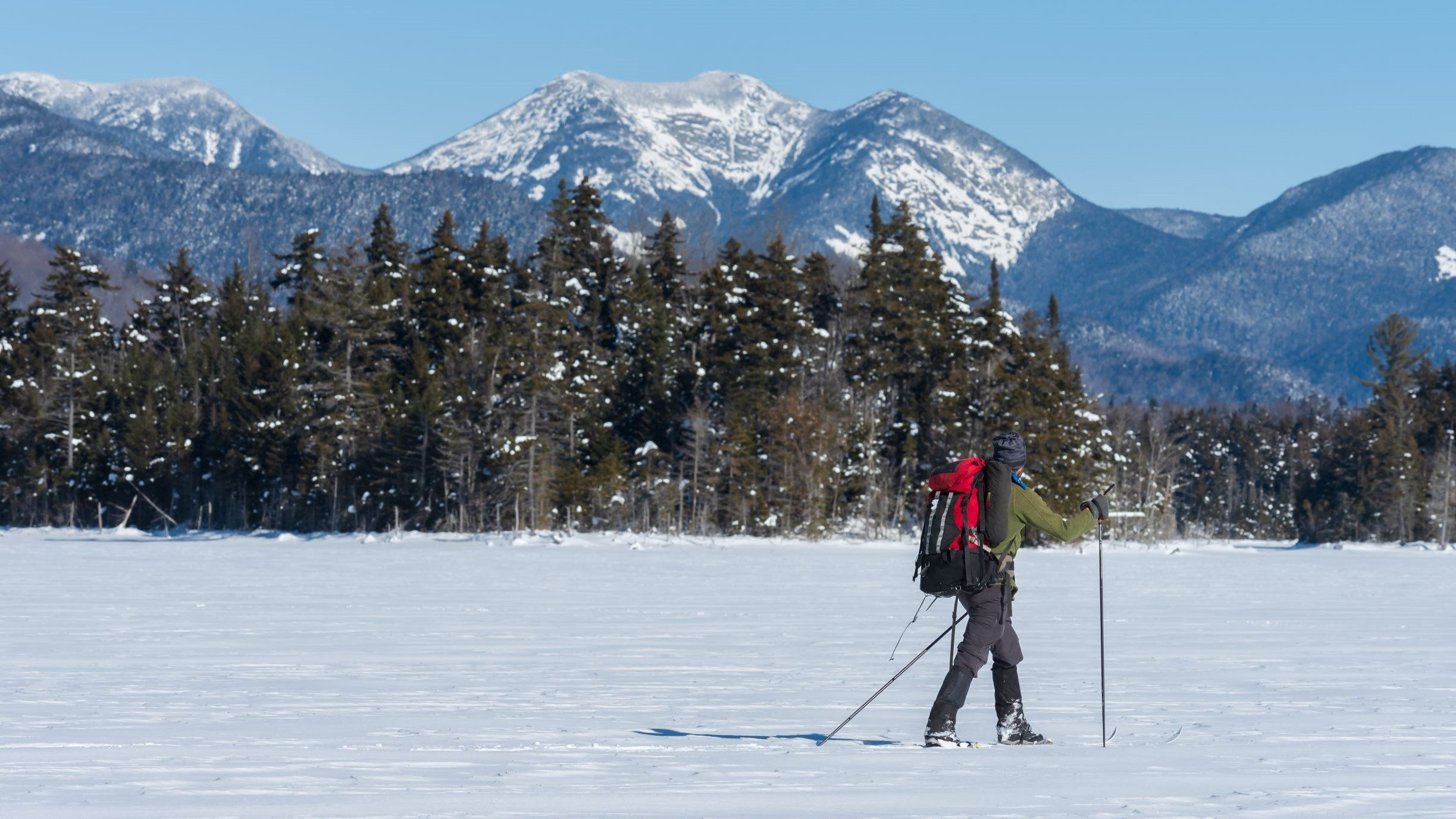 A man skis on a frozen lake while looking at a mountain