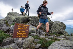 People hiking on a mountain summit near a sign
