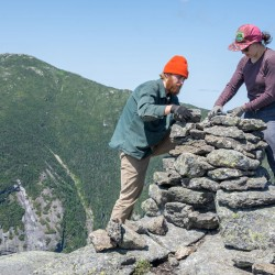 Two trail workers building a cairn