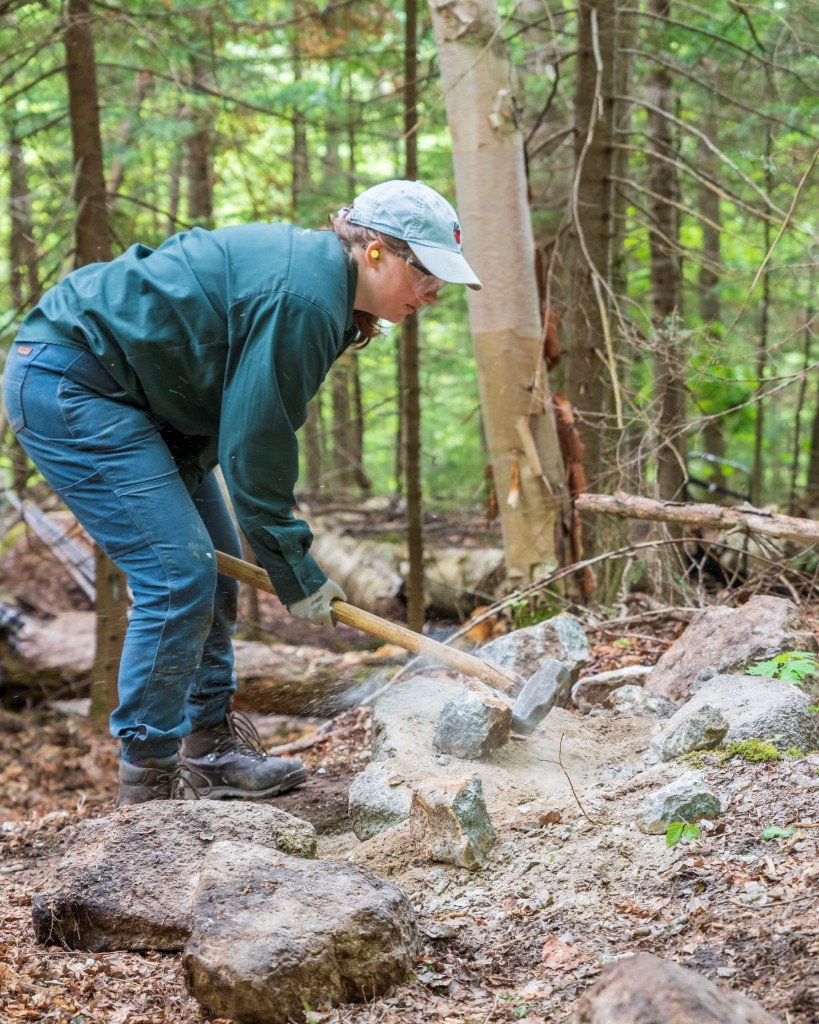 A trail worker crushes a rock with a hammer