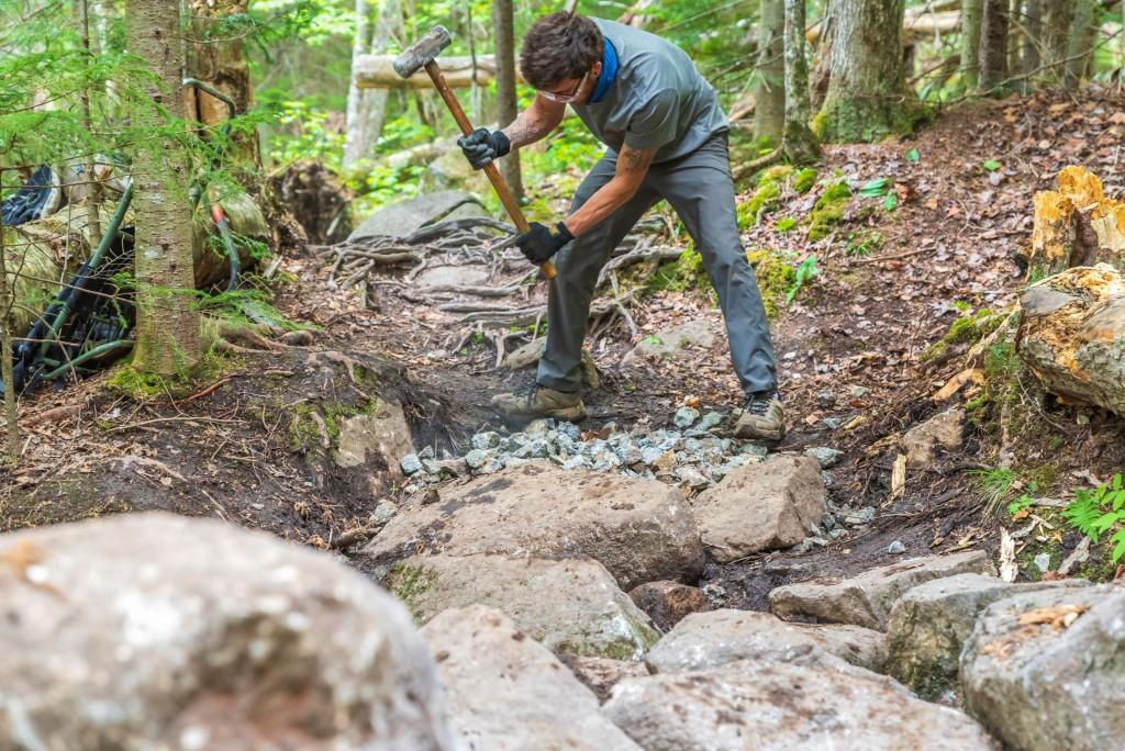 A trail worker swings a hammer