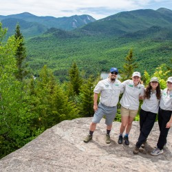 Four people standing on a mountain summit