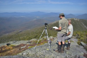 Two people stand behind a camera on a mountain