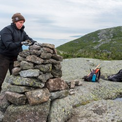 A person working on a rock cairn