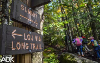 A trail sign with people in the background